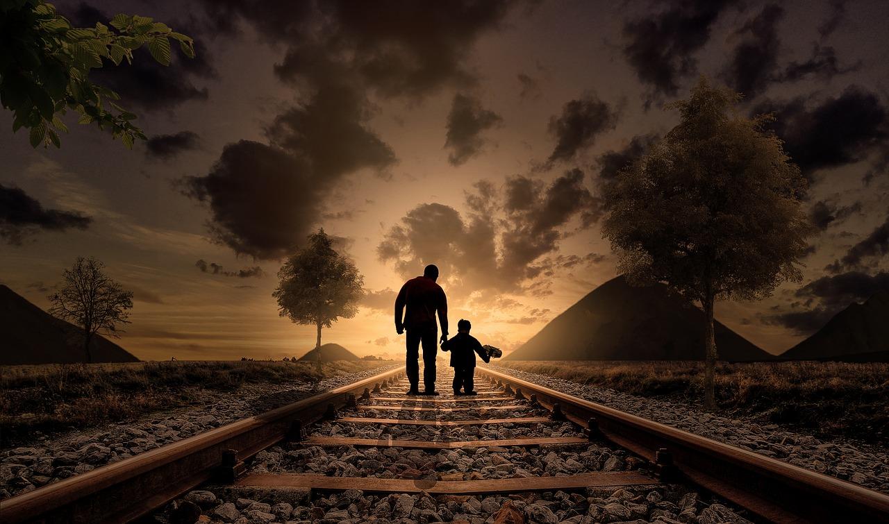 Pai e filho de mão dada, a caminha nuns carris em direção ao por-do-sol