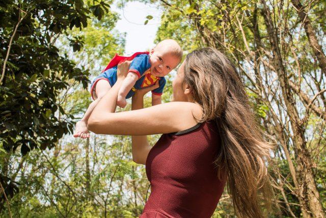 Mãe com bebé ao colo. Bebé está vestido de super-homem