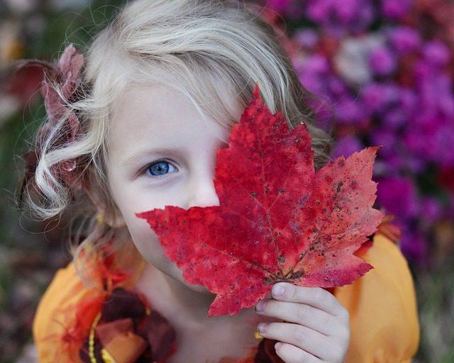 menina com uma folha de outono
