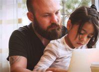 Pai e filha a ver o computador