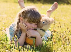 Menina sorridente, deitada na relva, abraçada a um urso de peluche