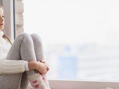 Menina sentada a uma janela